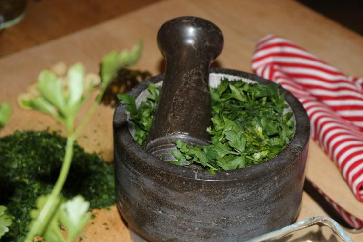 Kräuter mit Mörser und Stößel. Klassisches grünes Pesto - hier mit Petersilie statt Basilikum - muss kalt und zügig hergestellt werden, damit sich der Geschmack dieser kalten Sauce vollständig entfalten kann. Foto (c) Regiothek.
