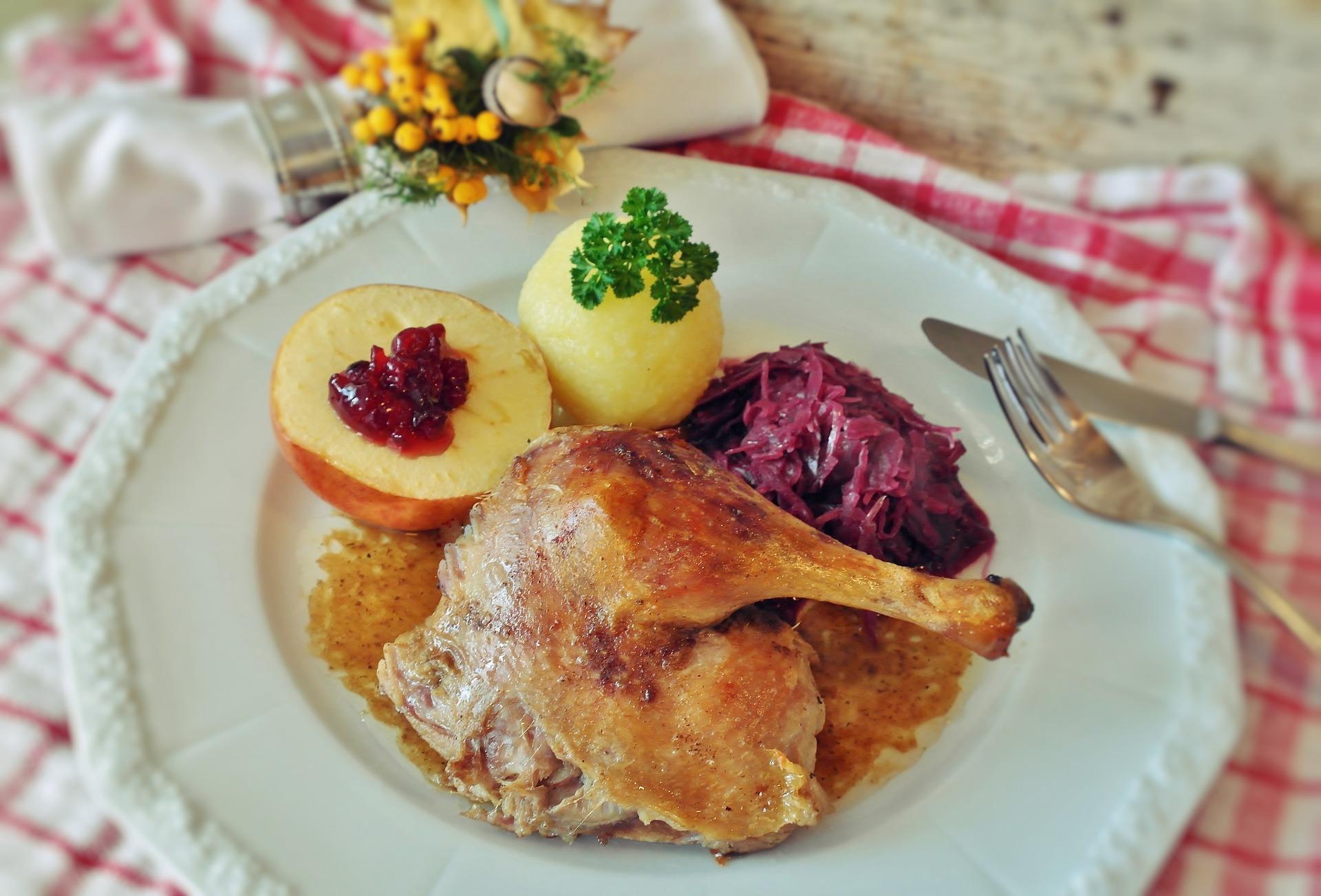 Entenbraten mit Blaukraut, Kartoffelknödel und Apfel als Beilage.
