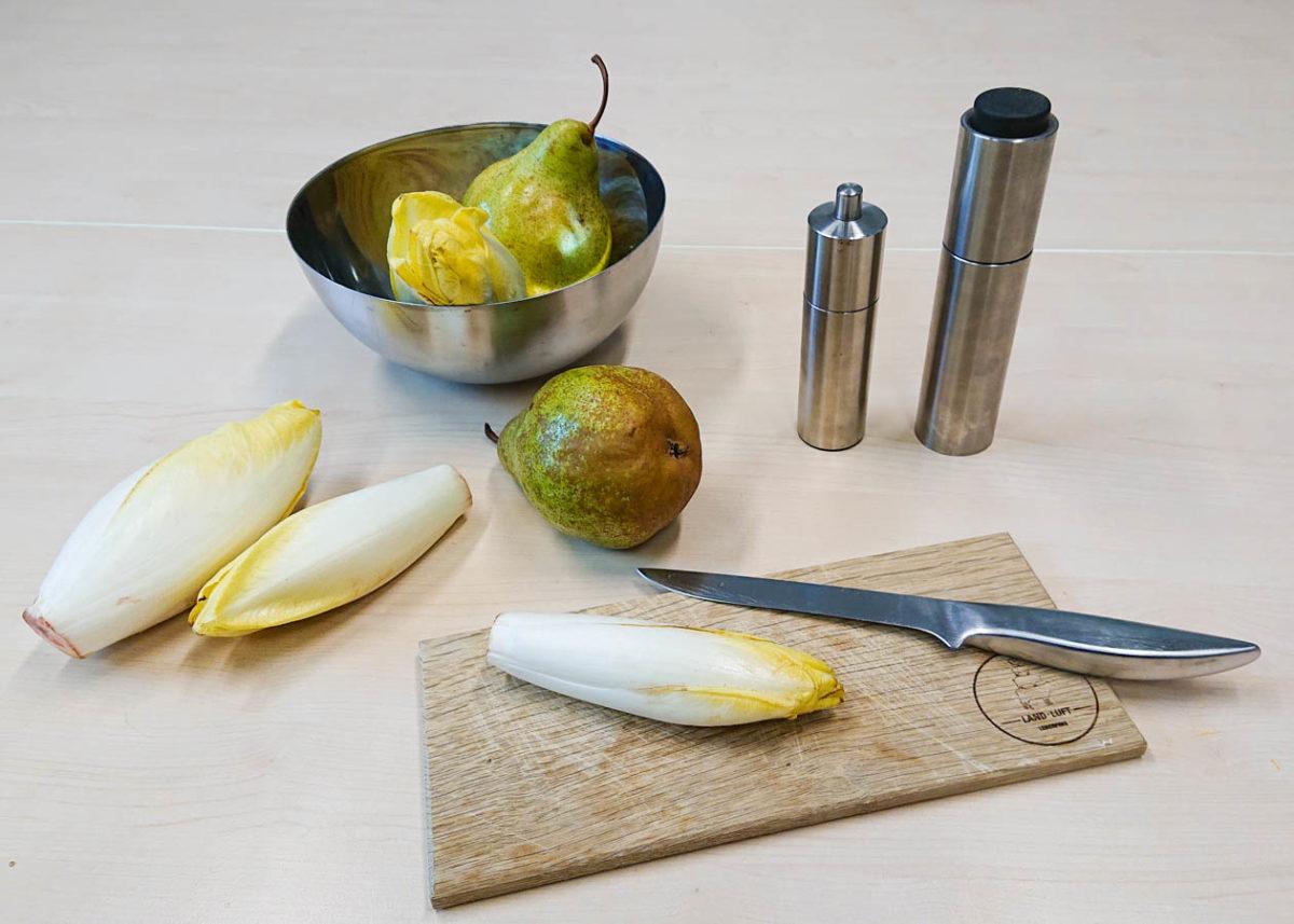 Birnen und Chicoreé vor der Zubereitung in einer Metall-Schale und auf dem Tisch verteilt. Auf einem Schneidebrett liegt ein Chicoreé und ein Messer. Daneben metallische Salz- und Pfefferstreuer.