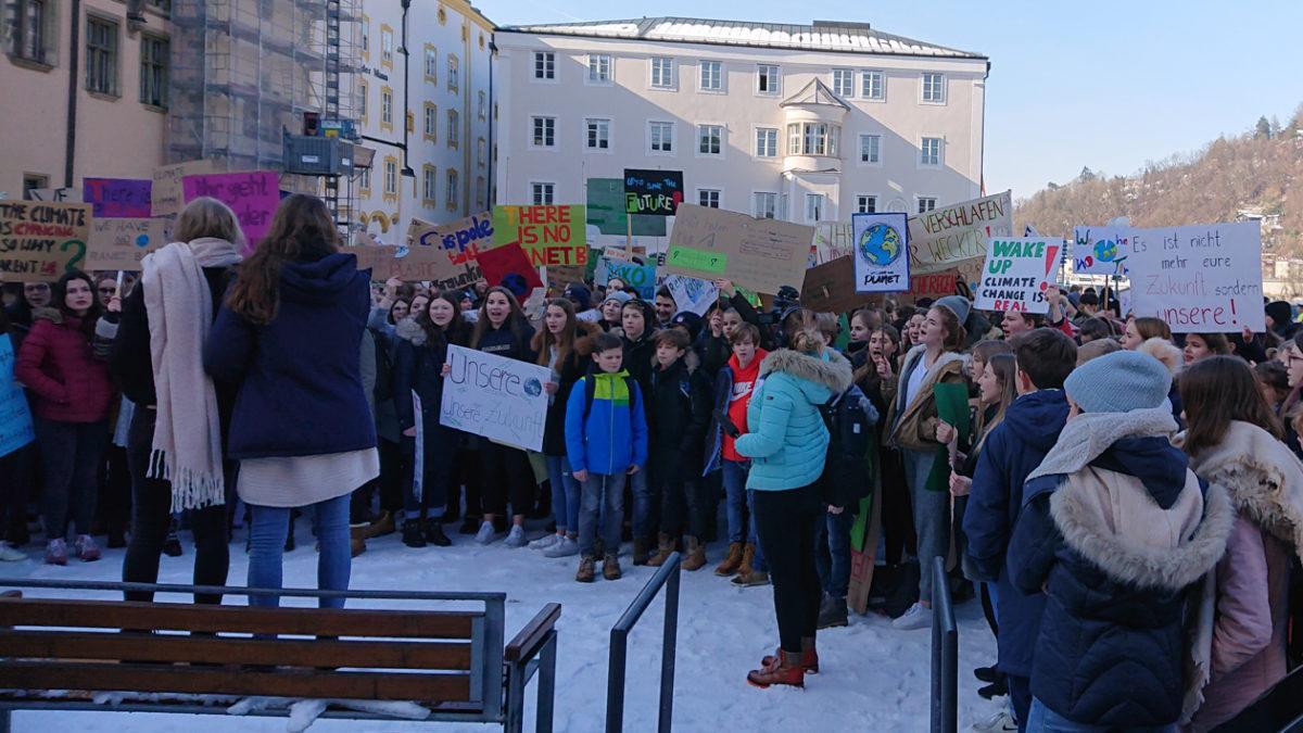 Schüler demonstrieren auf dem Passauer Rathausplatz. Zwei Schülerinnen stehen auf einer Bank, den Blick zur Menge gewandt und halten ein Megafon. Die Schüler halten Plakate in die Höhe.