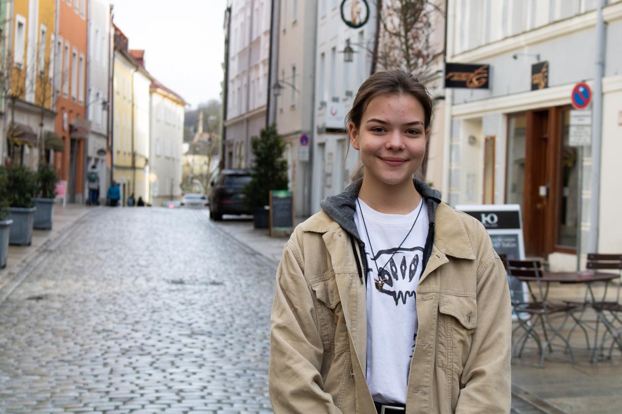 Franziska Maurer trägt eine beige Jacke, darunter einen grauen Hoodie, dessen Kapuzenansatz zusehen ist. Darunter trägt sie ein weißes T-Shirt mit einer schwarzen Grafik auf der Brust. Eine Anhänger aus Messing hängt an einem schwarzen Lederband, sie trägt ihre dunklen, längeren Haare zu einem Dutt gebunden. SIe lächelt leicht mit festem Blick in die Kamera. Im Hintergrund verschwimmt die Passauer Theresienstraße.