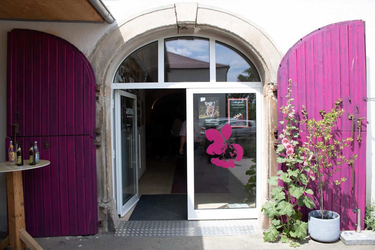 Gläserne Eingangstür vom Langlebenhof mit lilanen Türläden und Topfpflanzen im Vordergrund.