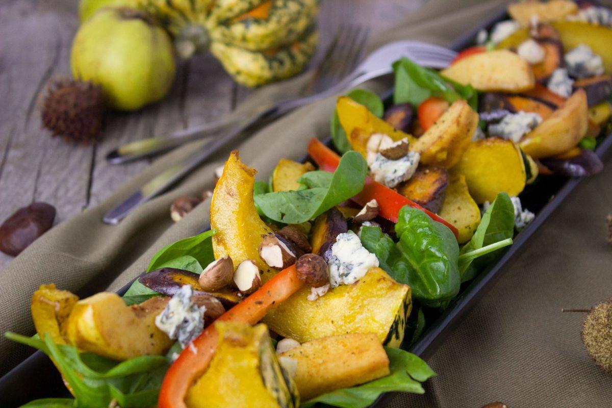 Spinatsalat mit Kürbis, Nüssen und Gorgonzola auf einer länglichen Platte angerichtet.