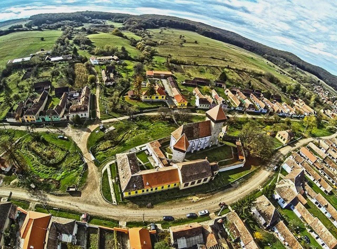 Probsdorf (Stejarisu) in Siebenbürgen aus der Luft. Im Zentrum des Bildes steht eine Kirche, um die herum sich Höfe mit hellbraunen Dächern und weißen oder bunt gestrichenen Fassaden anordnen. Um und im Dorf gibt es viel grün, die Straße gleicht eher einem Feldweg.