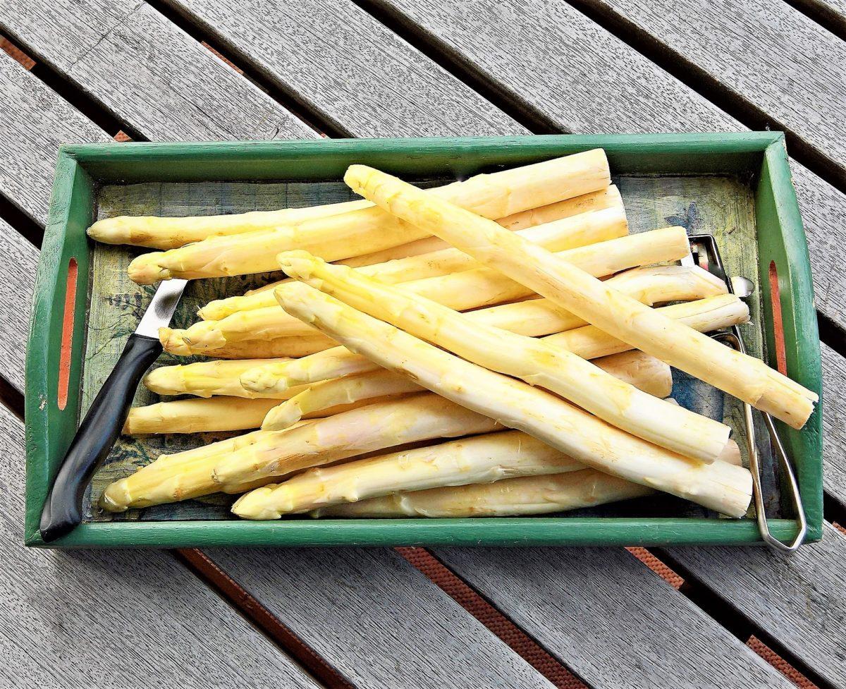 Weißspargel auf einem grünen Tablett. Daneben liegen Messer und Schäler. Das Tablett steht auf einem grauen Holztisch.
