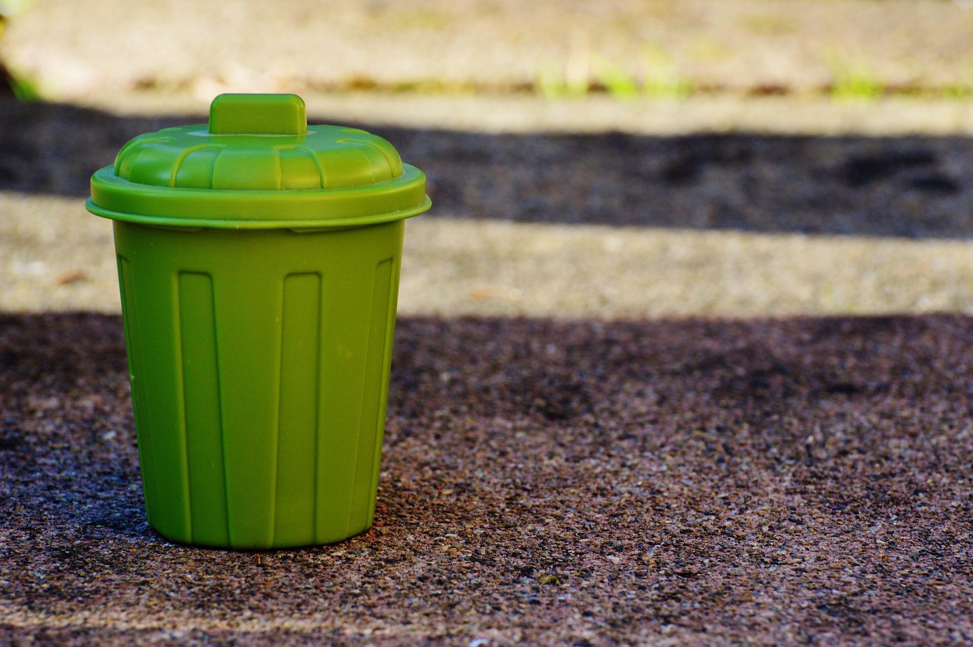 Ein kleiner, grüner Mülleimer steht auf der Straße.