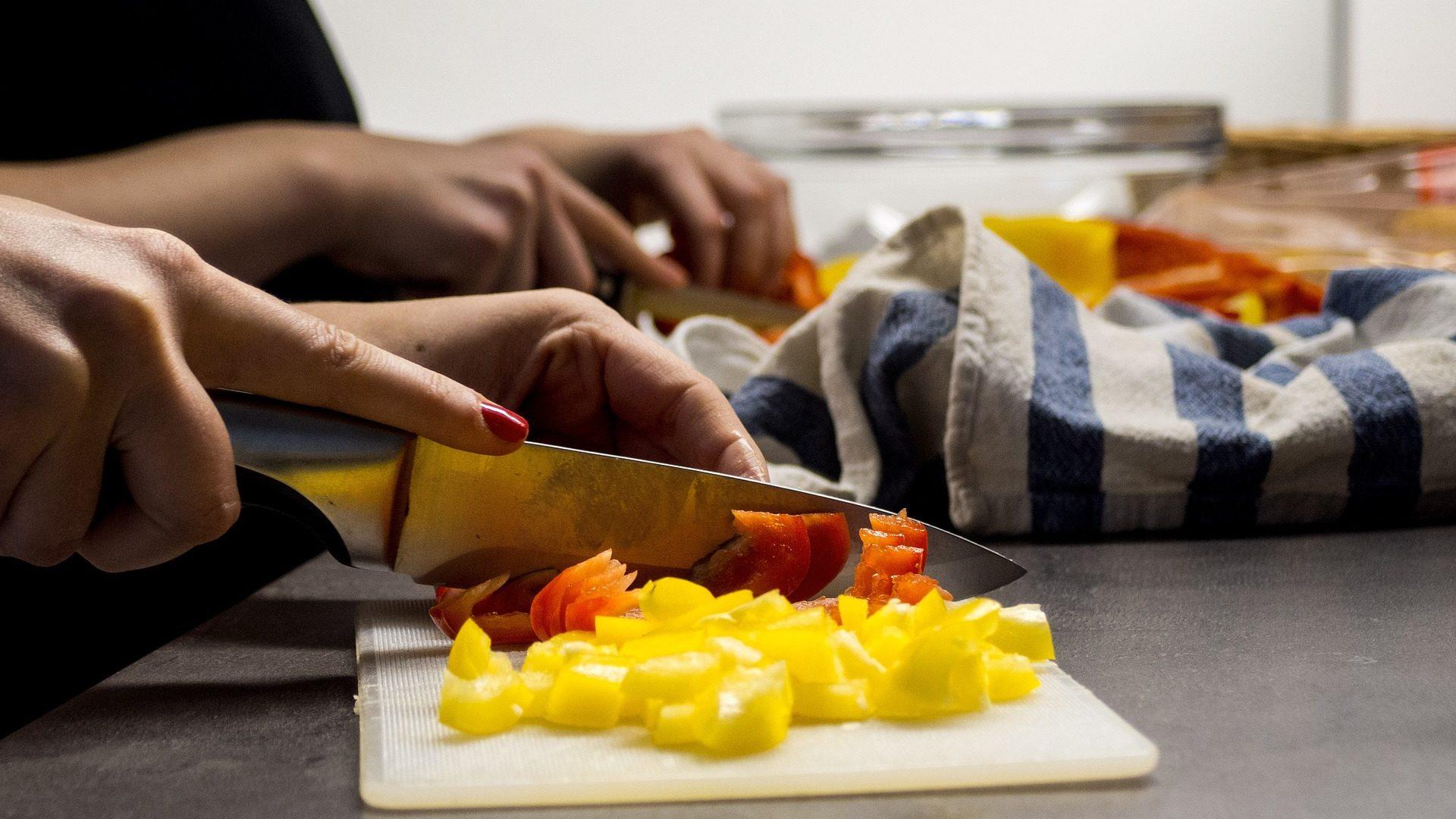 Eine Frau schneidet Paprika auf einem Schneidbrett klein.