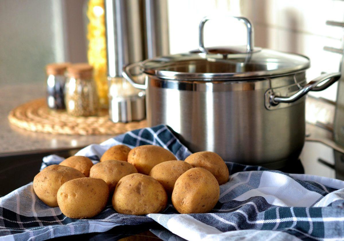 10 mittelgroße Kartoffeln liegen auf einem blau-weißen Spültuch. Dahinter steht ein Topf auf dem Herd. Im Hintergrund sind Gewürze aud der Küchenplatte angedeutet.