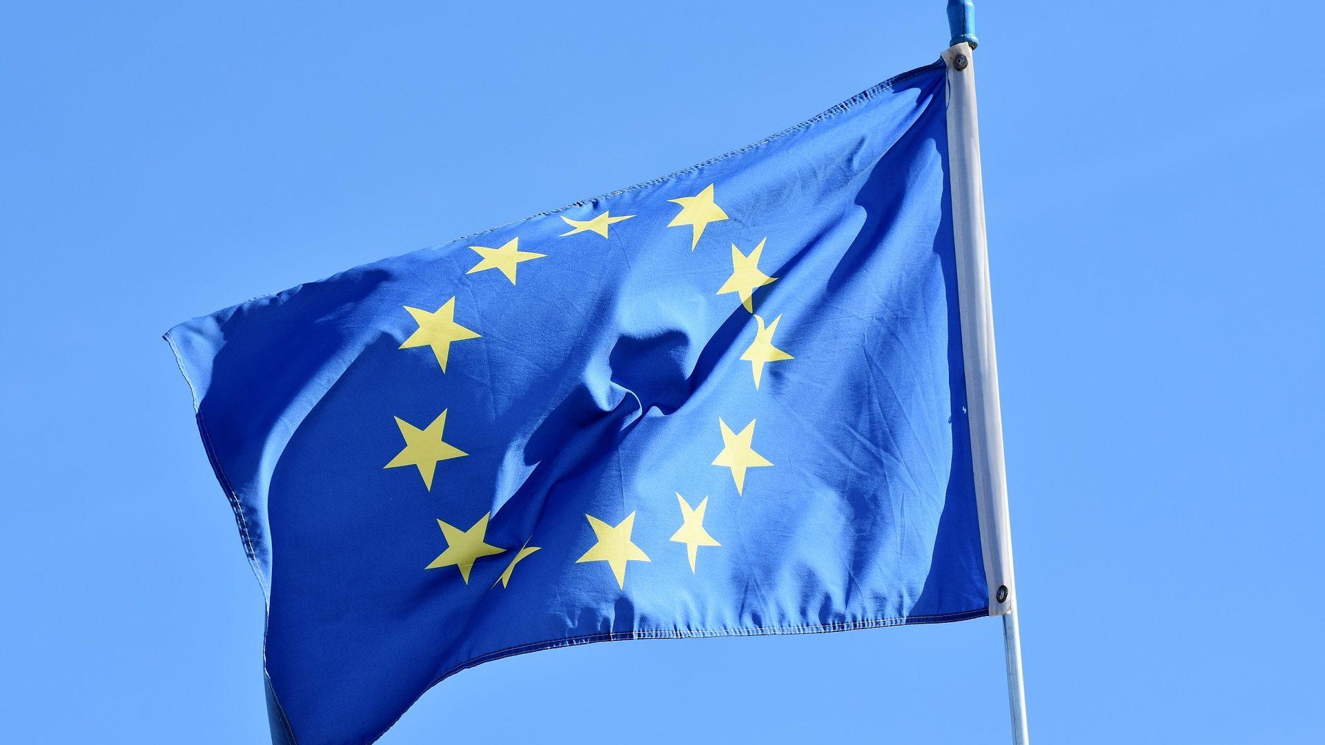 Die gehisste europäische Flagge (gelbe, kreisförmig angeordnete Sterne auf blauem Grund) flattert an einem Fahnenmast vor blauem Himmel.